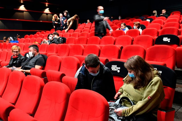 People wearing protective face masks await the beginning of a cinema screening in Sarajevo. Picture: Elvis Barukic
