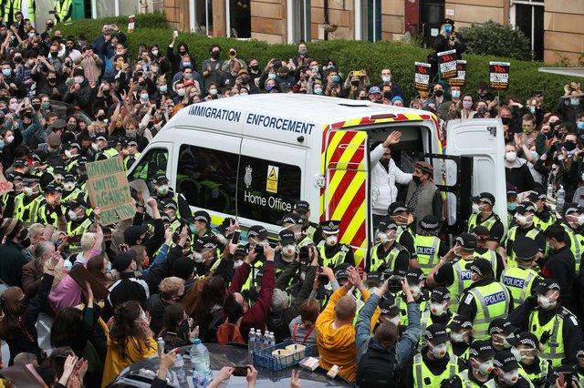 One of two men are released from the back of an Immigration Enforcement van accompanied by Mohammad Asif, director of the Afghan Human Rights Foundation, in Kenmure Street, Glasgow which is surrounded by protesters