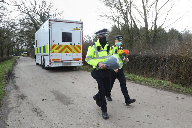 Police officers carry flowers from members of the public at Great Chart Golf and Leisure near Ashford in Kent following the discovery of human remains in the hunt for missing Sarah Everard. The Met Police announced on Wednesday that a diplomatic protection officer held over the disappearance of Sarah Everard has been arrested on suspicion of murder.