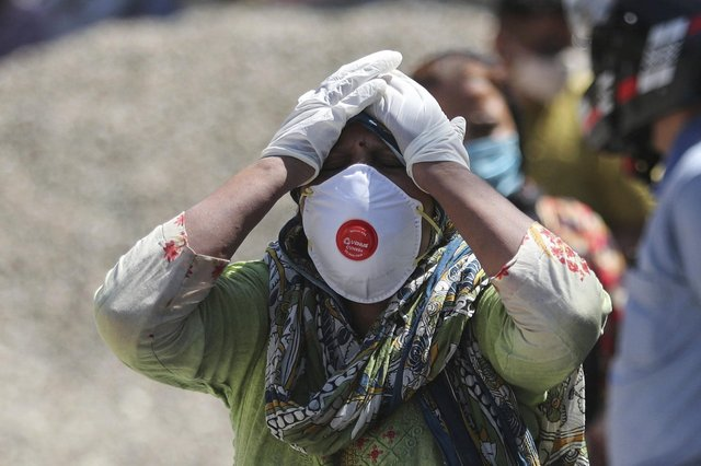 A relative of a person who died of COVID-19 reacts at a crematorium in Jammu, India.  (AP Photo/Channi Anand, File)