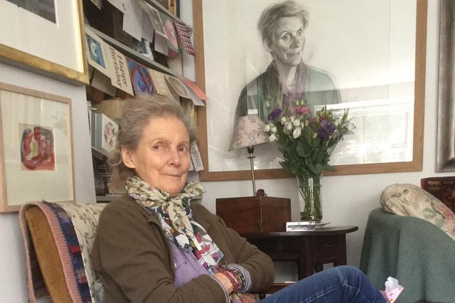 Pat Semple pictured with a portrait by fellow artist John Byrne