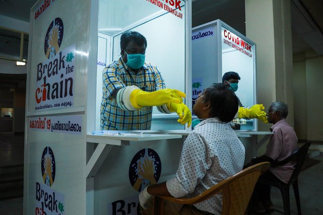 Medical staff collect samples from people at a Walk-In Sample Kiosk (WISK) to test for Covid at the Ernakulam Medical College in Kerala (Picture: Arun Chandrabose/AFP via Getty Images)