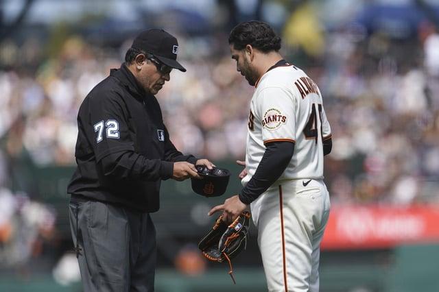 San Francisco Giants pitcher Jose Alvarez, right, has his cap inspected by umpire Alfonso Marquez. Picture: Jeff Chiu/AP