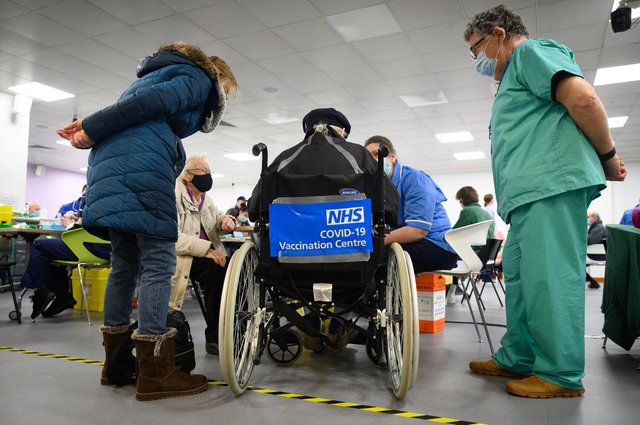 A man waits in a wheelchair for his coronavirus vaccination. Photo by Leon Neal / POOL / AFP