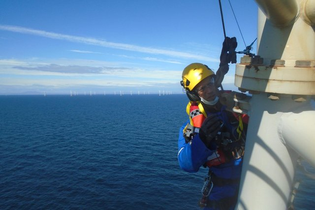 A PD&MS rope access technician working at a wind farm off the coast of Scotland.