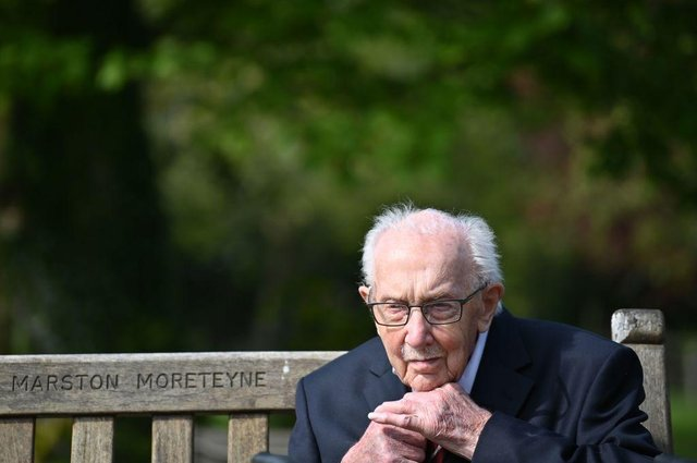 Captain Tom Moore does up his tie as he sits on a bench in the village of Marston Moretaine (Photo: JUSTIN TALLIS/AFP via Getty Images)