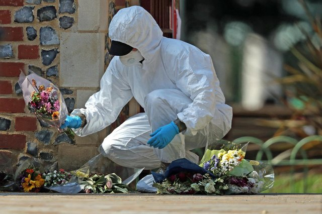 A forensic officer searches floral tributes laid at Forbury Gardens, Reading, where three people were killed and three seriously injured (Picture: Steve Parsons/PA Wire)