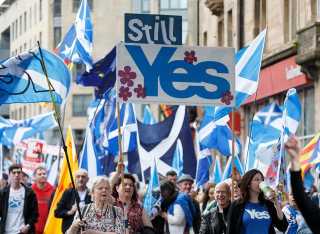 People taking part in the March for Independence wave Saltires as they process through Glasgow city centre.