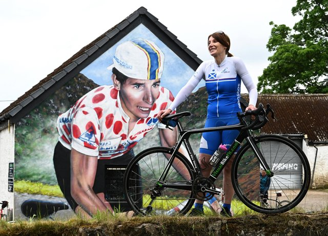 Philippa York, who previously competed as Robert Millar, beside the mural in Lennoxtown which celebrates the cyclist's achievements at the first Briton to be crowned 'King of the Mountains' in the Tour de France. Picture: John Devlin