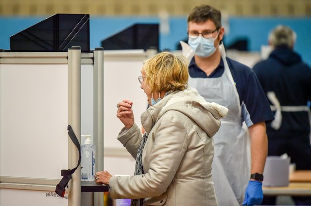 A woman takes a swab for a lateral flow test. Picture: PA Media.