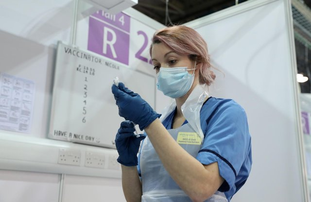 A vaccinator in Glasgow prepares a shot of Covid-19 vaccine. Photo by Andrew Milligan - WPA Pool/Getty Images