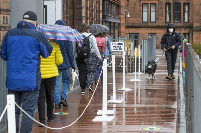 People queue to vote in the rain outside the polling station at Notre Dame Primary School in Glasgow.