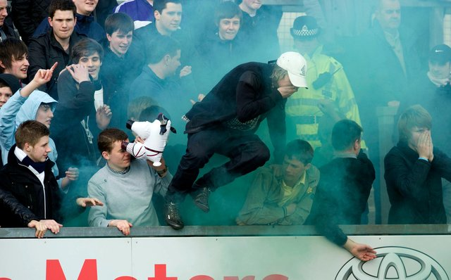 Falkirk fans try to escape flares let off by their supporters in a game with a Ross County in March 2012. (Photo by Sammy Turner/SNS Group).