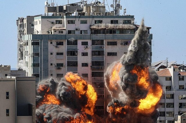A ball of fire erupts from the Jala Tower as it is destroyed in an Israeli airstrike in Gaza City.