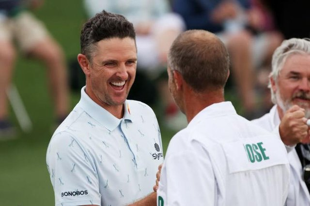 Justin Rose fist bumps his caddie, David Clark, after setting the pace in the 85th Masters at Augusta National Golf Club. Picture: Kevin C. Cox/Getty Images.