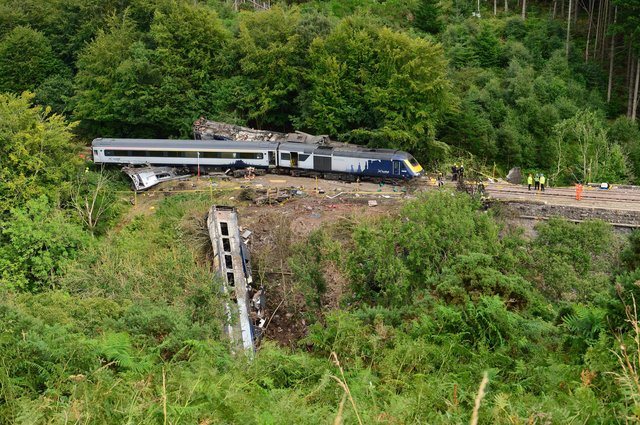 Members of the emergency services inspect the debris and derailed carriages at the scene of the train crash near Stonehaven on August 12 last year. Picture: Ben Birchall/AFP/Getty