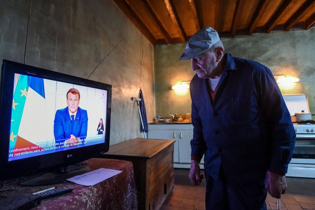 86-year-old retired farmer Henri Boutfol prepares his dinner as he  watches French President Emmanuel Macron's televised speech at his farm in Happonvilliers, near Chartres, eastern France, on March 31, 2021(Photo by JEAN-FRANCOIS MONIER/AFP via Getty Images).