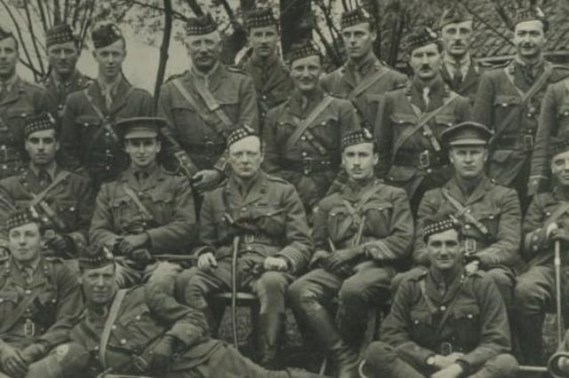 Lieutenant-Colonel Winston Churchill, seated centre wearing a Glengarry bonnet, and Andrew Dewar Gibb, also in a Glengarry, pose for a picture with other officers during the First World War