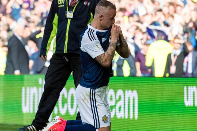Leigh Griffiths kisses the Scotland crest after curling in his second free-kick in the famous 2-2 draw with England for which the fourth anniversary is now rolling round. (Photo by Alan Harvey/SNS Group).