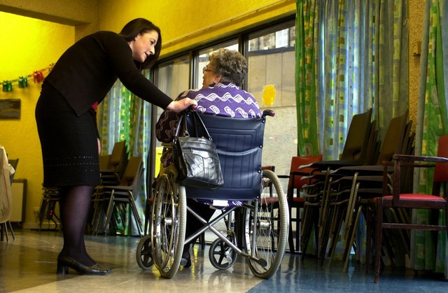 Nurse in a care home talking to an elderly woman in a wheelchair