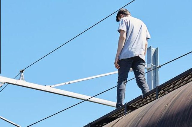 A youth on top of a train beneath 25,000-volt power cables in a Network Rail safety video. (Picture: Network Rail)