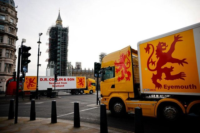 Lorries from Scotland drive past the Houses of Parliament in a protest action by fishermen against post-Brexit red tape and coronavirus restrictions, which they say could threaten the future of the industry, in London on January 18, 2021. (Photo by Tolga Akmen / AFP)