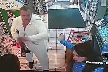 CCTV footage shows a Port Glasgow shopkeeper being spat on as a man in a unicorn onesie and the woman he was with try to rob two bottles of Buckfast