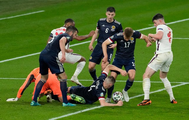 Scotland's Scott McTominay and Stuart Armstrong scramble the ball with Declan Rice of England.