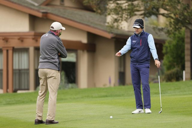 Russell Knox talks to a rules official on the first hole during the final round of the AT&T Pebble Beach Pro-Am at Pebble Beach Golf Links in California. Picture: Ezra Shaw/Getty Images.