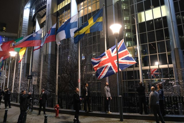 Workers at the European Parliament lower the British flag from the row of flags of EU member states outside the parliament in Brussels on January 31, 2020 - Brexit day