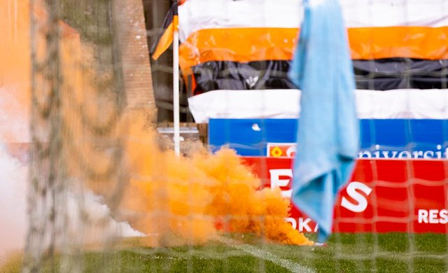 An orange flare billows out smoke as it lies on the Tannadice turf. Picture: SNS