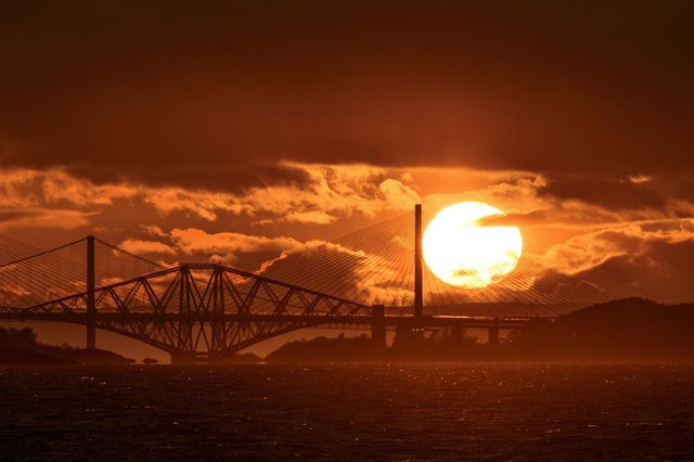 Photographer Tom Duffin, 57, captured a giant sun with clouds and the iconic bridges contrasted against it picture: SWNS