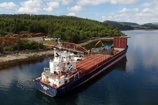 Timber being loaded and shipped by boat on Ardcastle timber pier in West Argyll.