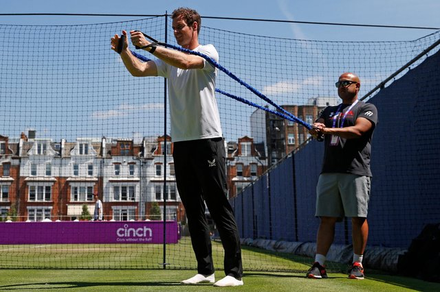 Andy Murray does stretching exercises as he practises ahead of today'sfirst-round match against France's Benoit Paire