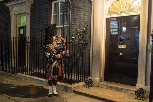 A piper of the Scots Guards plays outside 10 Downing Street, London, to welcome guests to a Burns' Night supper (Picture: Dominic Lipinski/PA)