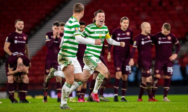 Celtic players celebrate with distraught Hearts in the background.
