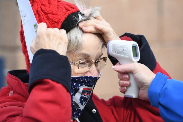 Fans have their temperature checked as a return of supporters to stadia is trialed during the Scottish Premiership match between Ross County and Celtic at the Global Energy Stadium, on September 12, 2020, in Dingwall, Scotland. (Photo by Craig Williamson / SNS Group)