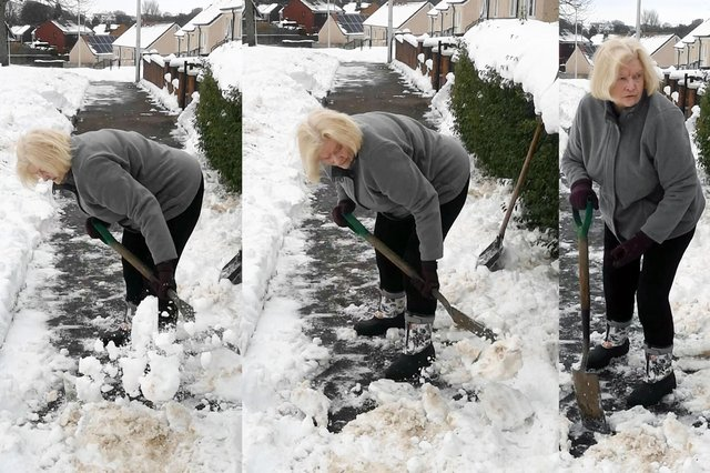 85-years-old Isabel Nicholson clearing snow outside her home in Redding.