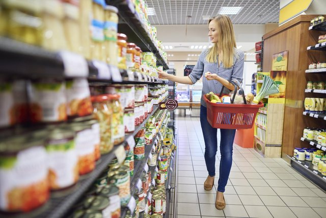 A woman buys products in a supermarket food aisle