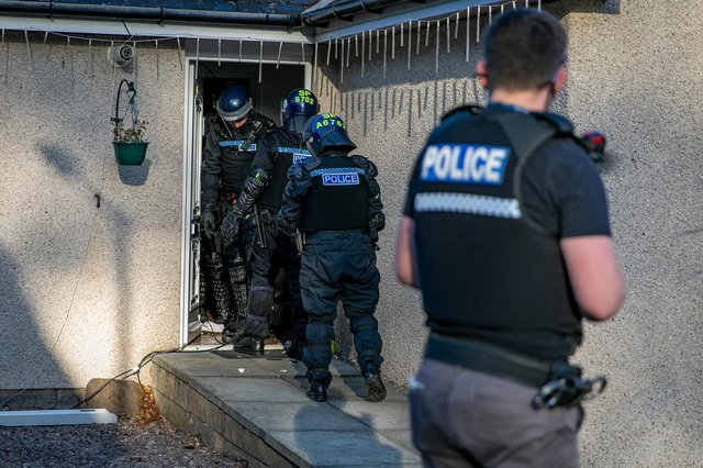 Police at one of the raided properties. Picture: Steven Brown/Police Scotland