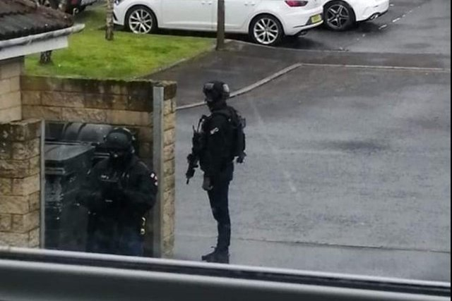 Armed officers pictured outside a property in Queens Crescent in Livingston. Picture: Steve Binnie.