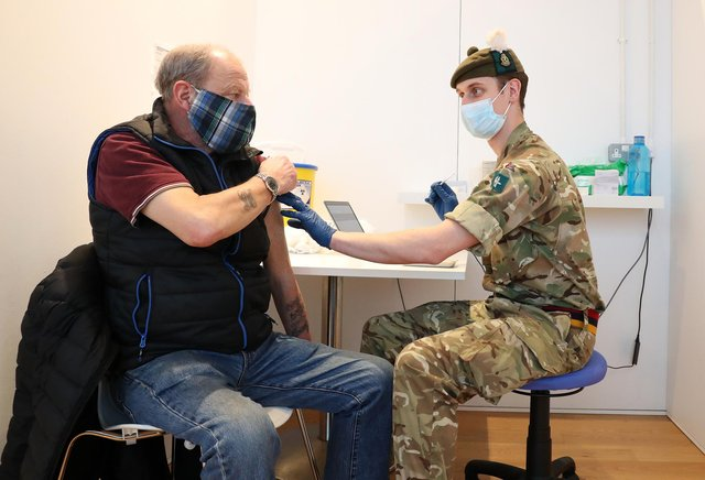 Derek Fraser from Edinburgh receives an injection of a coronavirus vaccine from military doctor Captain Robert Reid from 3 Medical Regiment who are assisting with the vaccination programme at the Royal Highland Showground near Edinburgh. Picture date: Thursday February 4, 2021.