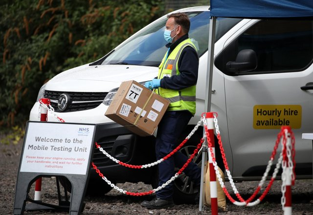 Staff from the Scottish Ambulance Service carry boxes of test kits from a van at a Covid Mobile Testing Unit in a car park in the Pollokshields area of Glasgow. Glasgow and Moray remain in Level 3 restrictions despite the rest of mainland Scotland moving to Level 2 on Monday. Picture date: Tuesday May 18, 2021.