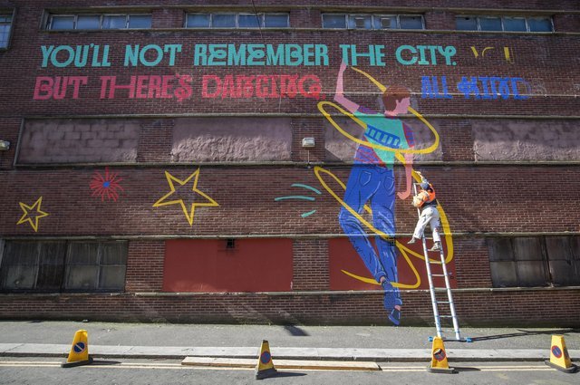 Glasgow School of Art graduate Chelsea Frew, one of the Cobolt Collective illustrators, works on part of the Shuggie Bain mural outside the Barrowland Ballroom in the east end of Glasgow.