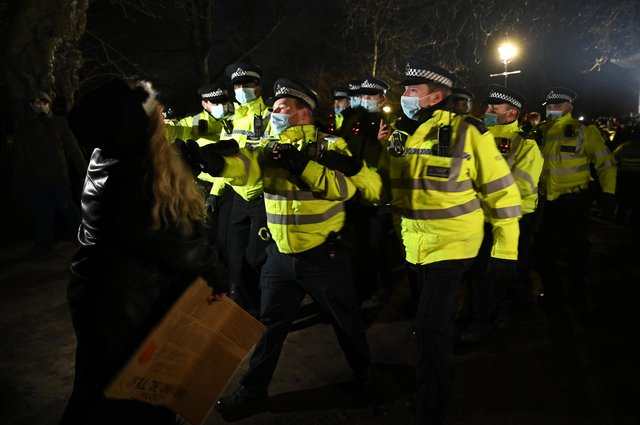 LONDON, ENGLAND - MARCH 13: Police Officers arrest a woman during a vigil on Clapham Common, where floral tributes have been placed for Sarah Everard. Picture: Leon Neal/Getty Images