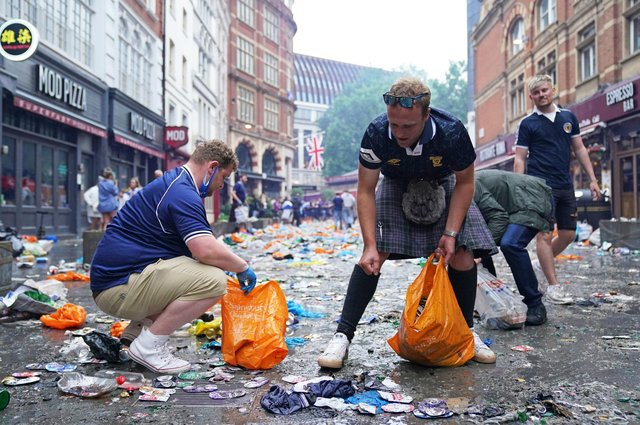 Scotland fans clean up litter in Irving Street  near Leicester Square, London  (Pic: Kirsty O'Connor/PA Wire)