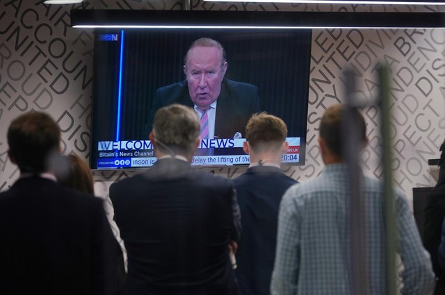 Staff in the green room watching a television screen showing presenter Andrew Neil broadcast from a studio, during the launch event for new TV channel GB News.