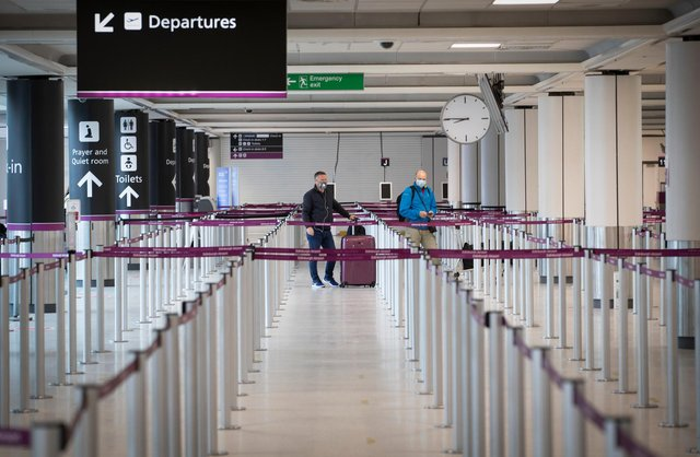 Passengers, wearing a protective face masks, wait at the check-in area at Edinburgh Airport