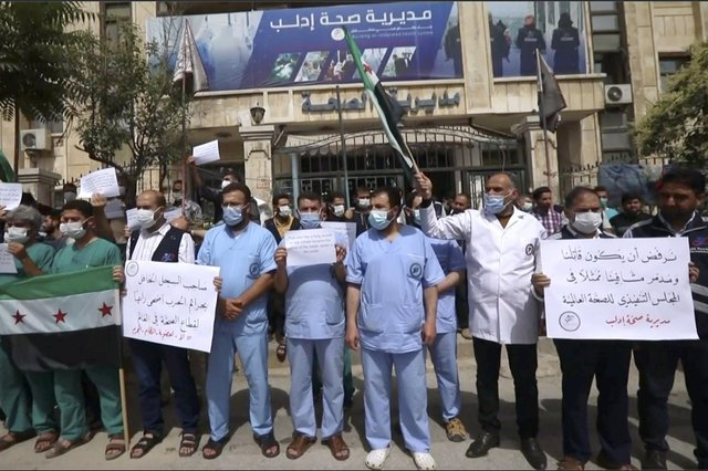 Dozens of medical workers protest against a decision to grant Syrian President Bashar Assad's government a seat on the executive board of the World Health Organisation in Idlib, Syria (Picture: AP)