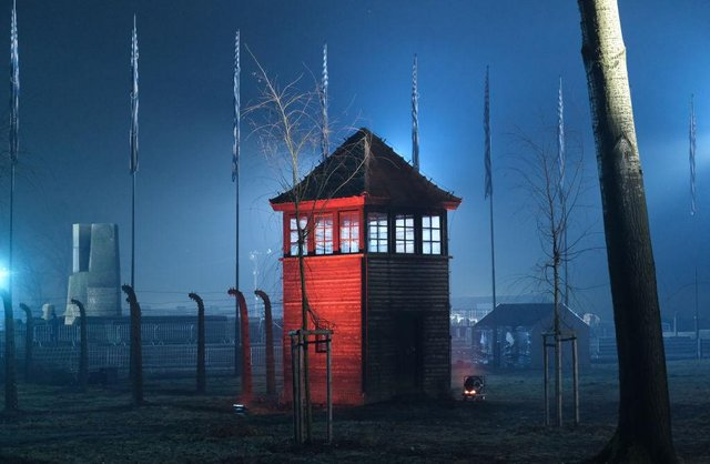 A guard tower stands illuminated at the former Auschwitz-Birkenau concentration camp near the Auschwitz Memorial. (Pic: Getty Images)